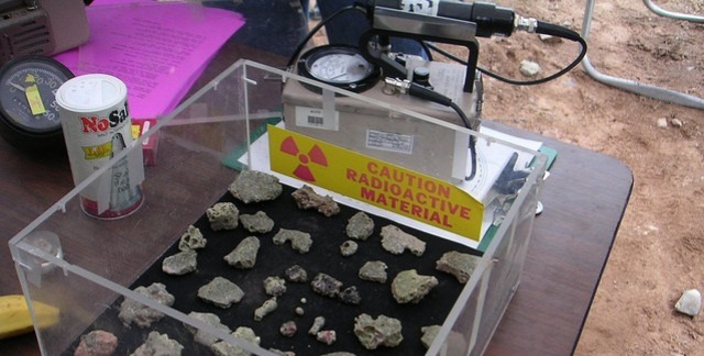 Trinitite pieces and a geiger counter (which measures radioactivity).